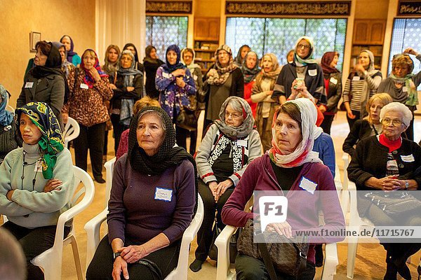 Non-Muslim women from the local Mission Viejo  CA  community don the hijab  or traditional Muslim female head scarf during an informational visit to a mosque. Note Muslim female parishioners in background.