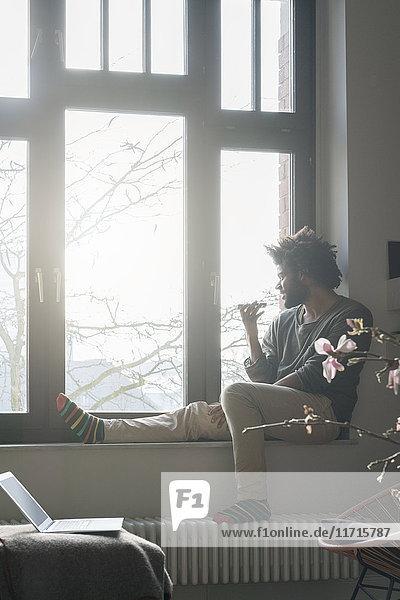 Mann sitzt auf der Fensterbank im Wohnzimmer und schaut nach draußen und spricht mit dem Smartphone.