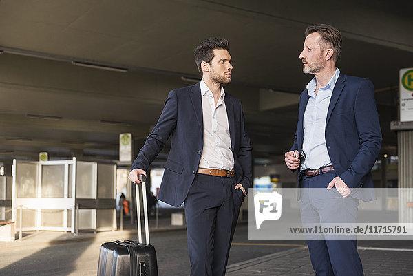 Zwei Geschäftsleute mit Rollkoffer stehen am Busbahnhof