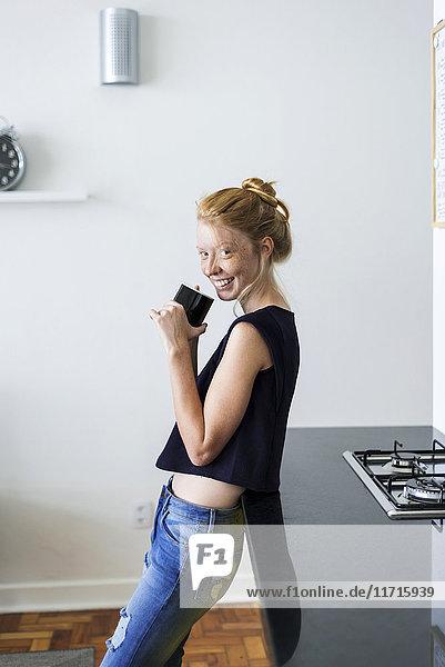 Junge Frau steht in der Küche und trinkt Kaffee.