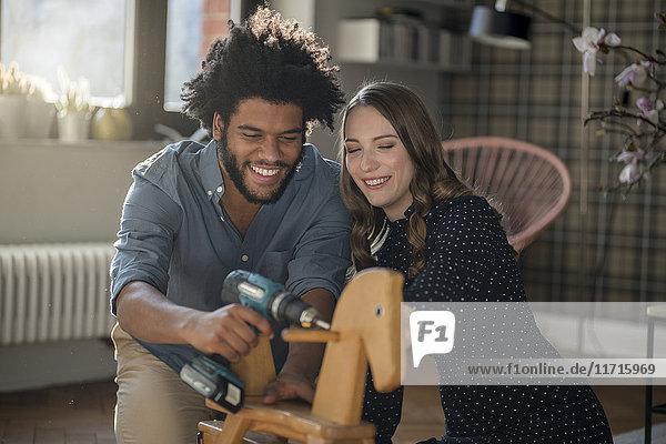 Lächelndes Paar montiertes Schaukelpferd mit Akku-Bohrmaschine