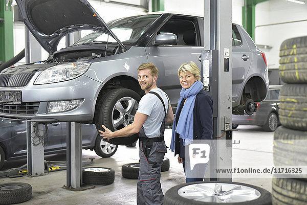 Porträt eines lächelnden Automechanikers mit Kunde in der Werkstatt am Auto