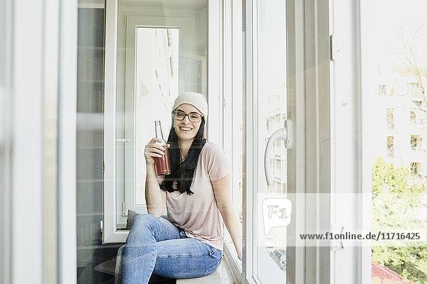 Porträt einer lächelnden jungen Frau mit Flasche am Fenster