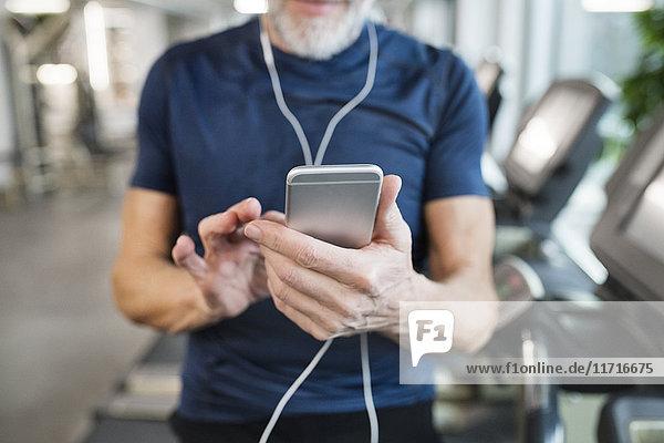 Senior Mann mit Smartphone im Fitnessstudio