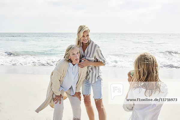 Kleines Mädchen beim Fotografieren am Strand ihrer Mutter und Großmutter