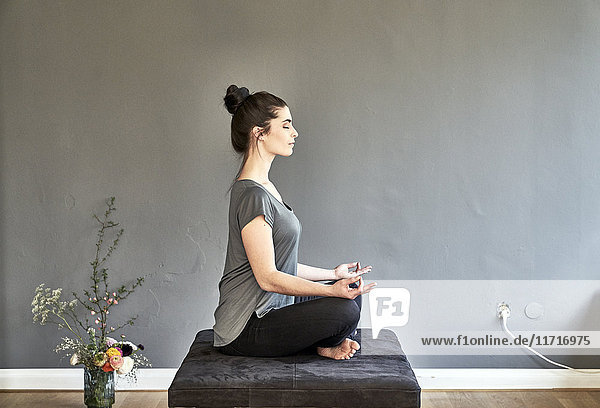Junge Frau sitzt auf der Lounge und macht Yoga.