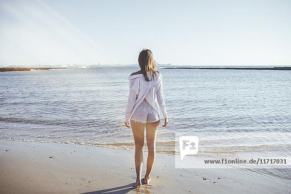 Rückansicht der Frau am Strand mit Blick aufs Meer