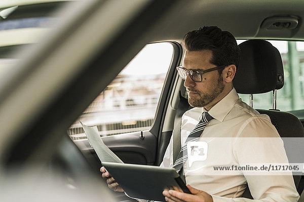 Erfolgreicher Geschäftsmann sitzend im Auto mit digitalem Tablett