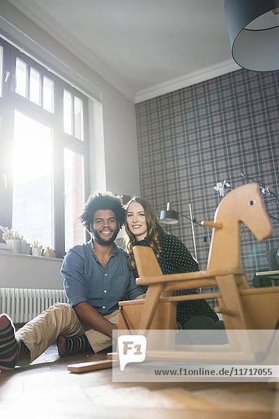 Lächelndes Paar schaut in die Kamera vor dem Schaukelpferd