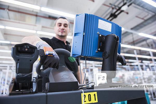 Mann mit tragbarem Scanner am Schlepperzug in der Fabrikhalle