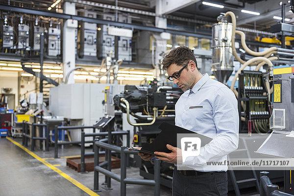 Mann schaut sich Dokumente in der Fabrikhalle an