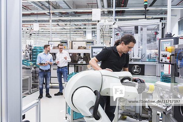 Mann  der den Montageroboter in der Fabrik bedient  mit zwei Männern im Hintergrund  die die Montage überwachen.