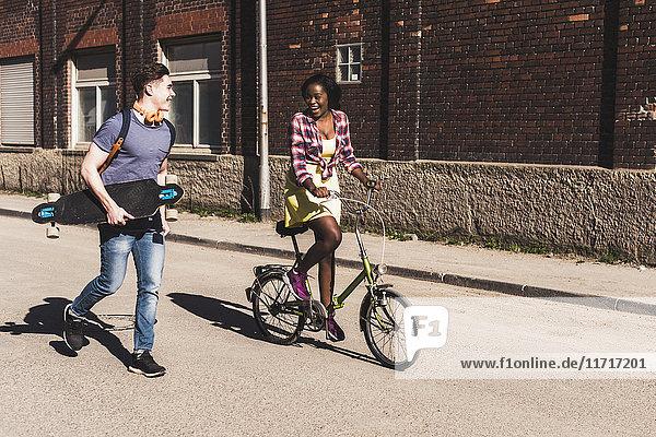 Junges Ehepaar mit Fahrrad und Skateboard auf der Straße