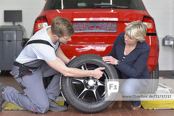 Kfz-Mechaniker mit Kunde und Reifen in der Werkstatt am Auto