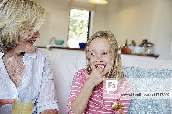 Porträt eines lächelnden kleinen Mädchens  das Sandwich isst  während Großmutter ihr zusieht