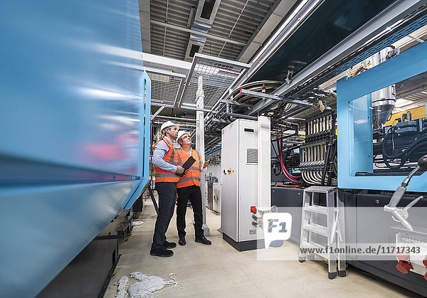 Zwei Männer mit Sicherheitswesten und Schutzhelmen untersuchen das System in der Fabrik.