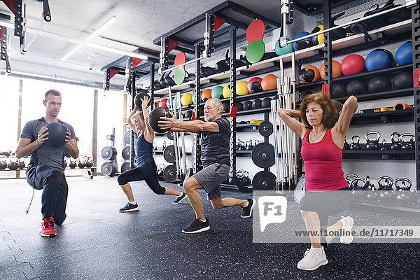 Gruppe von fit Senioren mit Personal Trainer im Fitnessstudio mit Medizinbälle