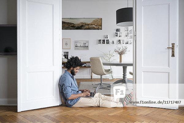 Mann zu Hause auf dem Boden sitzend  arbeitet mit Laptop im Türrahmen