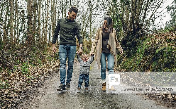 Schwangere Frau  die im Herbst mit ihrer Familie im Wald spazieren geht.