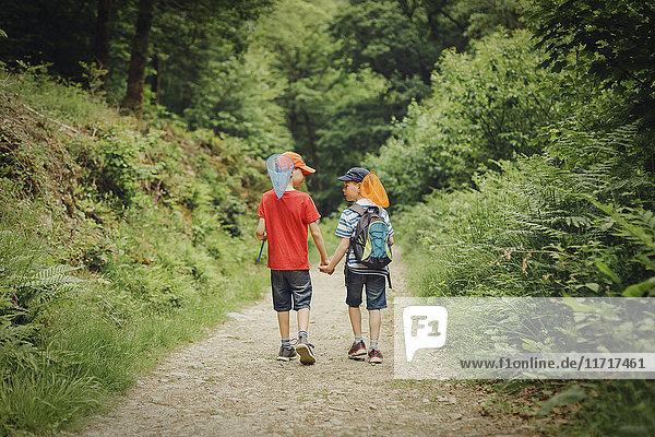 Zwei Jungen  die Hand in Hand mit Dip-Netzen gehen
