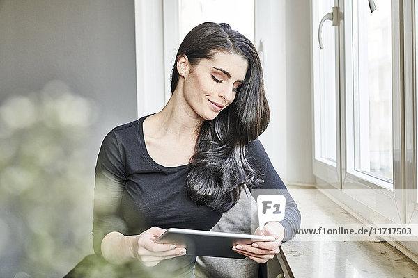 Lächelnde junge Frau mit Tablette am Fenster
