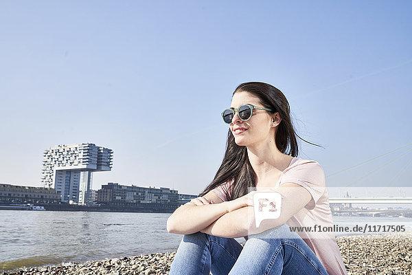 Deutschland  Köln  junge Frau entspannt am Rhein