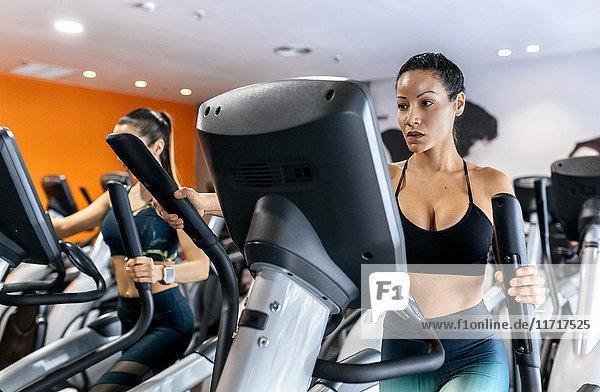 Zwei Frauen  die mit einem Ellipsentrainer im Fitnessstudio trainieren.