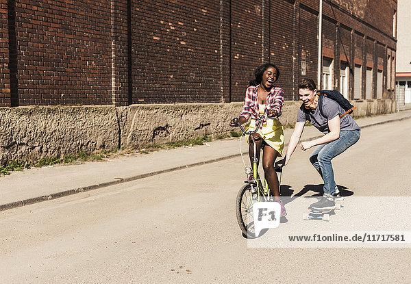Junge Frau auf dem Fahrrad zieht jungen Mann  stehend auf Skateboard