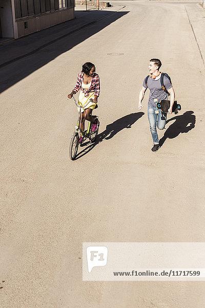 Glückliches Paar beim Laufen und Radfahren auf der Straße