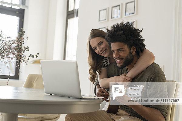 Lächelndes Paar vor dem Laptop im Wohnzimmer  Mann beim Gitarrespielen
