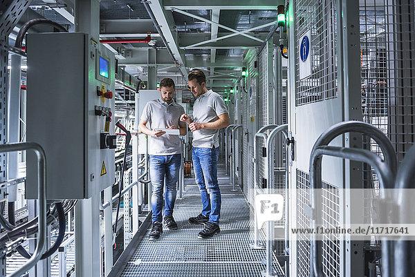 Zwei Männer im automatisierten Hochregallager beim Betrachten von Tabletten