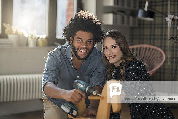 Lächelndes Paar beim Anblick der Kameramontage Schaukelpferd mit Akku-Bohrmaschine