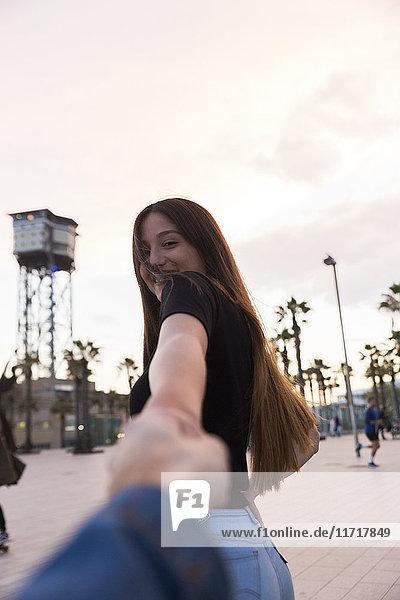 Spanien,  Barcelona,  glückliche junge Frau hält Hand