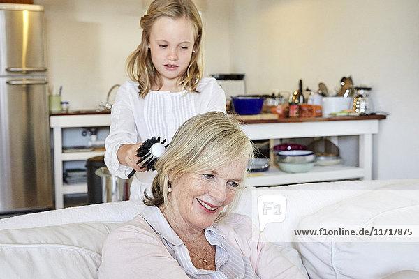 Kleines Mädchen bürstet die Haare ihrer Großmutter