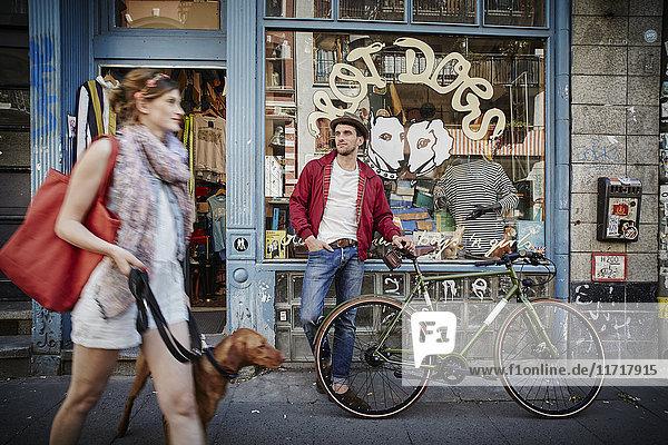 Deutschland  Hamburg  St. Pauli  Mann mit Fahrrad vor dem Vintage-Shop  Frau mit Hund im Auslauf