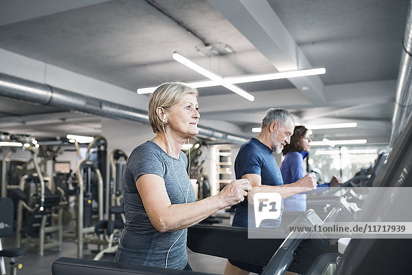 Gruppe von fit Senioren auf Laufbändern im Fitnessstudio