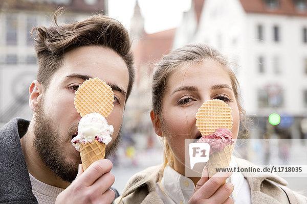 Lustiges Porträt eines jungen Paares beim Eis essen