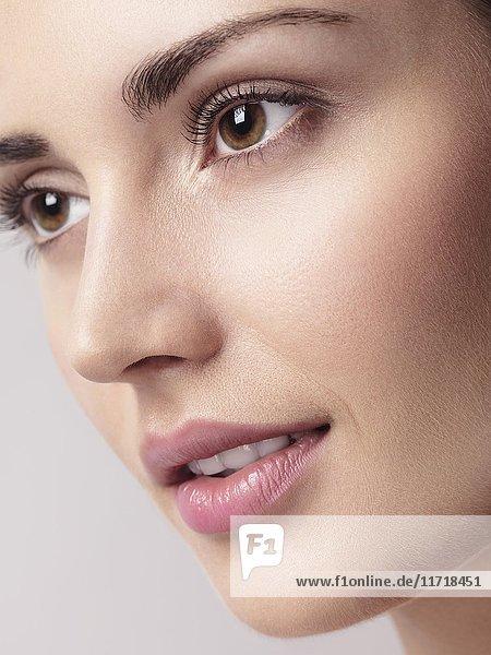 Nahaufnahme einer jungen schönen Frau  Gesicht mit braunen Augen  sauberes natürliches Aussehen und glatte Haut