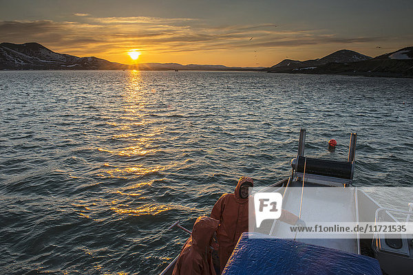 The sun sets over Kulukak Bay in the Bristol Bay region as a commercial fishing crew takes a break  Southwest Alaska  USA