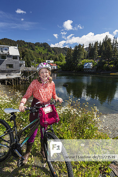 Young girl with her bicycle next to the Seldovia Slough on a sunny day  Southcentral Alaska  USA