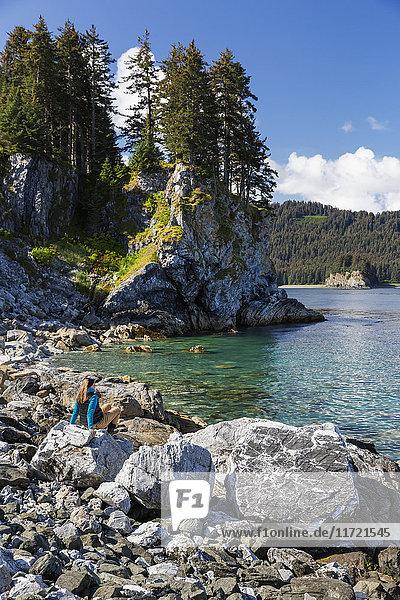 Woman sitting a top boulders along the rocky shoreline near Seldovia  Southcentral Alaska  USA