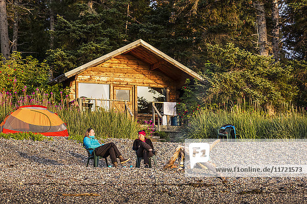 Two women relaxing in chairs on the shore of Hesketh Island with a public use cabin in the background  Southcentral Alaska  USA