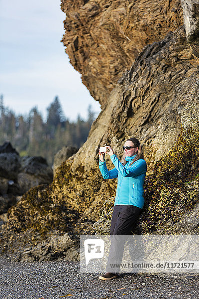 Woman photographing scenery with her smart phone along a Homer beach  Southcentral Alaska  USA