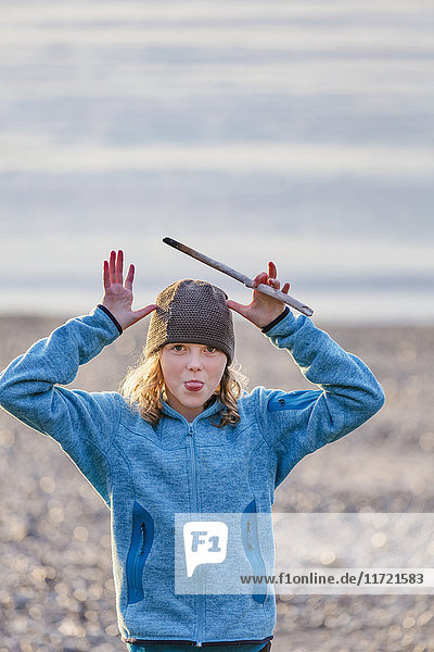 Young girl making faces to the camera along the beach of Seldovia  Southcentral Alaska  USA