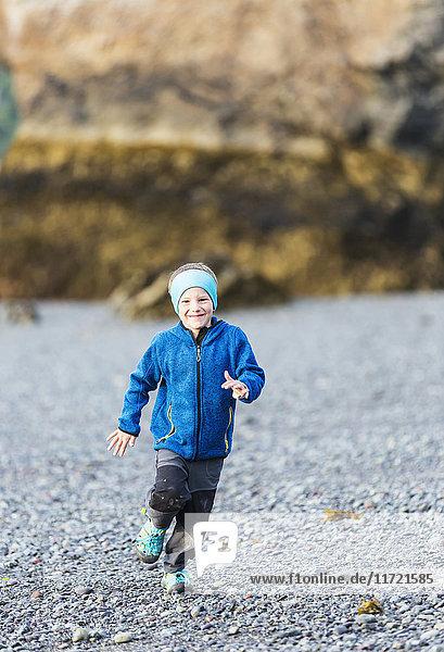 Young boy running on the beach  Hesketh Island  Southcentral Alaska  USA