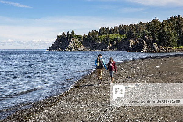 Mother and daughter walk on the beach  Seldovia  Southcentral Alaska  USA