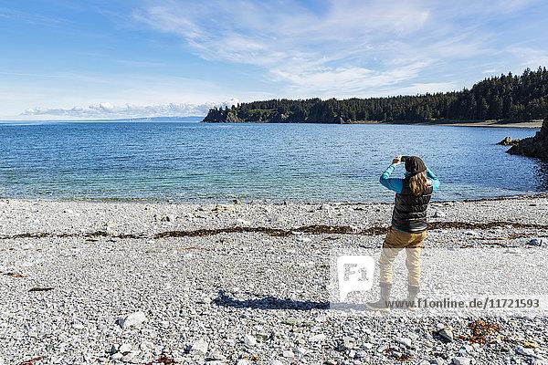 Woman photographing scenery along the beach at Seldovia  Southcentral Alaska  USA