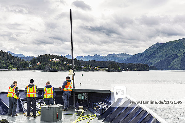 Ferry crewmen on the deck of a ferry arriving at Seldovia  Southcentral Alaska  USA