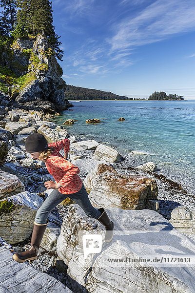 Young girl plays on rocks along the shore near Seldovia  Southcentral Alaska  USA