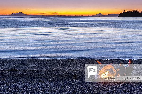 People enjoying a campfire on the beach at sunset  Hesketh Island  Southcentral Alaska  USA